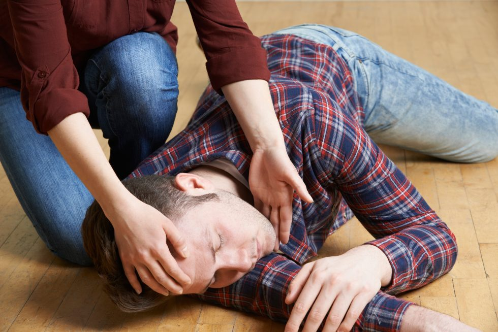 Woman Placing Man In Recovery Position After Accident